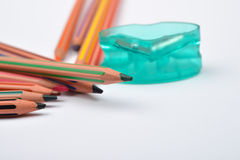 Picture of some pencils with stripes of different colors and pen. Cil sharpener on a white background. Selective focus Royalty Free Stock Photography