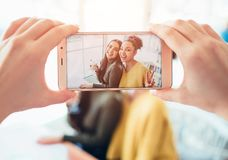 Picture of somebody taking a picture of two best friends that are happy to see each other. They have asked somebody to royalty free stock photography