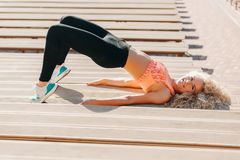 Picture of sports woman exercising among benches in summer day stock images