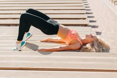 Picture of sports woman exercising among benches in summer day stock photography