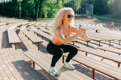 Picture of sports woman exercising among benches in summer day royalty free stock image