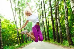 Picture of sports woman jumping in park stock images