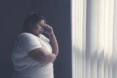 Stressed fat woman standing by the window. Picture of stressed fat woman having headache while standing by the window stock photography