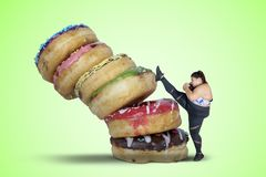 Strong fat woman kicking a pile of donuts stock image