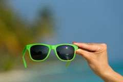 Picture of sunglasses on the tropical beach, vacation. Royalty Free Stock Photo