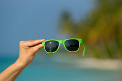 Picture of sunglasses on the tropical beach, vacation. Royalty Free Stock Photos
