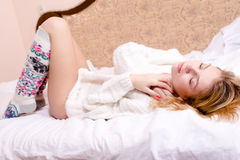 Picture of sweet sexy glamor young blond woman relaxing lying on her back in white bed in a sweater and socks. Beautiful sensual sexy young blond woman lying on Stock Photography