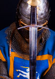 Picture of sword in hands. Praying knight with his sword Stock Photography