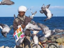 An african man and flying pigeons. stock photography