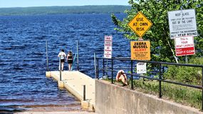 Road signs and children swimming on a dock stock photo