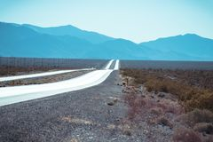 A long road through Death Valley. This picture taken in Death Valley Arizona shows a road clear road shining brightly as the sunlight is reflected on it with royalty free stock photos