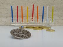 A glass Hannukiah filled with colourful candles on a white table with some scattered chocholate coins and a silver dreidel stock photo