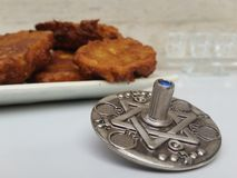 A plate full of Hannuka potato latkes fritters with a silver dreidel on a white table with a glass chanukiah in the background. Picture taken in my house for Royalty Free Stock Photos