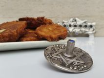 A plate full of Hannukah potato latkes fritters with a silver dreidel on a white table with a silver chanukiah in the background. Picture taken in my house for royalty free stock photography
