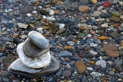 Stones piled up on the shore of a lake with stones in the background royalty free stock images