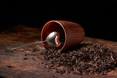 Picture of the tea strainer with dried tea leaves and sticks of cinnamon isolated on dark wooden background. Picture of the tea strainer with dried tea leaves royalty free stock photo