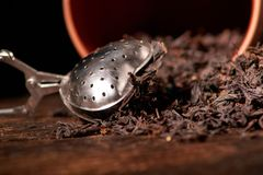 Picture of the tea strainer with dried tea leaves and sticks of cinnamon isolated on dark wooden background. Picture of the tea strainer with dried tea leaves royalty free stock photography