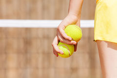 Picture of tennis player's hand with two balls Stock Images
