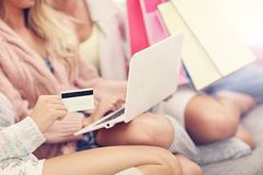 Three beautiful young women shopping online royalty free stock images
