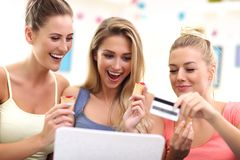 Three beautiful young women shopping online. Picture of three beautiful young women chilling at home Stock Image