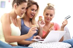 Three beautiful young women shopping online. Picture of three beautiful young women chilling at home Stock Images