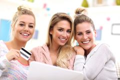 Three beautiful young women shopping online. Picture of three beautiful young women chilling at home Stock Photo