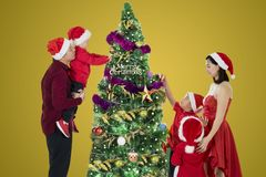 Children decorate a Christmas tree with their parents. Picture of three children helped by their parents for decorating a Christmas tree royalty free stock image