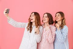 Picture of three cute women 20s wearing colorful striped pyjamas. Having fun and taking selfie using mobile phone during happy sleepover isolated over pink Royalty Free Stock Image