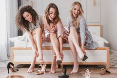 Picture of three gorgeous girls 20s wearing dresses trying on di. Fferent summer stilettos or high heels during bachelorette party in posh bedroom stock image