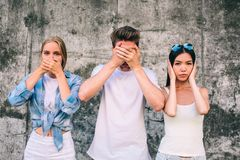 A picture of three young people standing together on grey background. Blonde girl is covering up her mouth with hands stock images