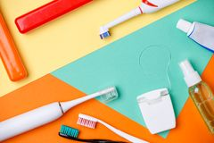 Picture of toothbrushes, tubes of pastes, floss. On orange, green and yellow background royalty free stock photo