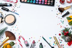 Picture on top of eye shadows, brushes, , tangerine, sugar cane ,nail polish on empty white table. Place for inscription in center royalty free stock photo