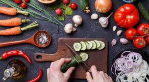 Picture on top of fresh vegetables, mushrooms, cutting board, oil, knife, hands of cook. On table Stock Images