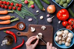 Picture on top of fresh vegetables, mushrooms, cutting board, oil, knife, hands of cook. On table Royalty Free Stock Photo