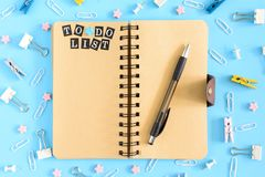 Picture from the top. Notepad on springs with an inscription To Do List. Chaotically scattered office supplies on a blue. Beautiful picture from the top. Notepad Stock Photo
