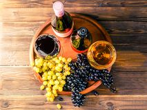 Picture on top of wine glass with wine, grapes black, green on wooden tray on table. In studio Stock Photos