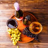 Picture on top of wine glass with wine, grapes black, green on wooden tray on table. In studio Stock Image