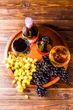 Picture on top of wine glass with wine, grapes black, green on wooden tray on table. In studio Royalty Free Stock Images