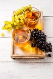 Picture on top of wooden box with two glasses of wine, black and green grapes Stock Images