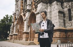 A picture of tourist standing near the big old building and looking to the map. Seems like this guy has lost in the big city and now he is trying to find his Royalty Free Stock Images