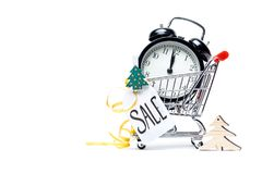 Picture of trolley with gold alarm clock, Christmas tree, greeting card, ribbon. On blank white background. Place for text Royalty Free Stock Photos