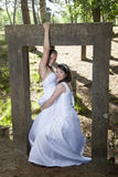 Picture of two brides under concrete object in nature surroundin Stock Images