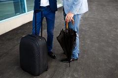 Picture of  two businessmen with umbrella and suitcase at station background Stock Photo
