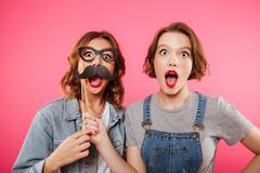 Funny ladies friends holding fake moustache and glasses. Picture of two funny ladies friends standing isolated over pink background. Looking camera holding fake Royalty Free Stock Photos