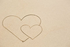 Picture of two hearts on wet beach sand Stock Image