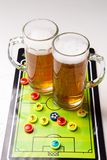 Picture of two mugs of beer, table football. On white table stock photography