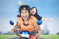 Two obese women riding scooter along city road. Picture of two obese women looks happy while riding a scooter along city road with blur motion Royalty Free Stock Photography
