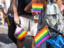 Two men and a woman holding rainbow gay flags in their pockets during a Gay Pride. Picture of two persons, holding and rainbow flags in their pockets, symbol of royalty free stock photo