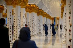 Women against wind at the Sheikh Zayed Mosque royalty free stock photo