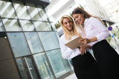Picture of two young beautiful women as business partners. Standing outside Royalty Free Stock Images